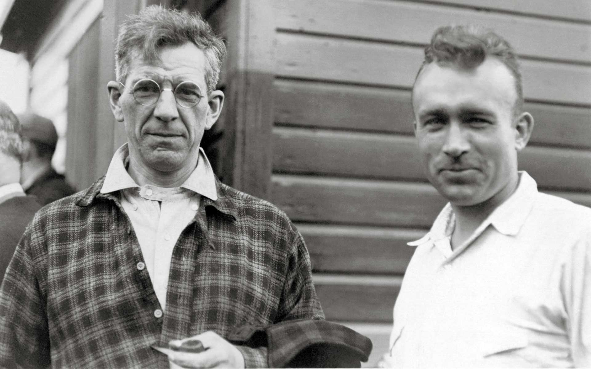 Old photograph: two men standing outside in front of a wood siding wall. At the left, a middle-aged man in plaid wearing round-lensed spectacles. At right, a younger man (30s) in a white collared shirt.