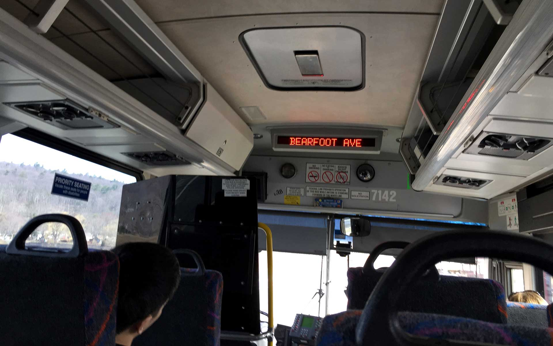 "Photograph: inside a New Jersey Transit bus with several passengers. Mountains are visible out of the left window. A dot matrix sign at the front reads ""Bearfoot Ave""."