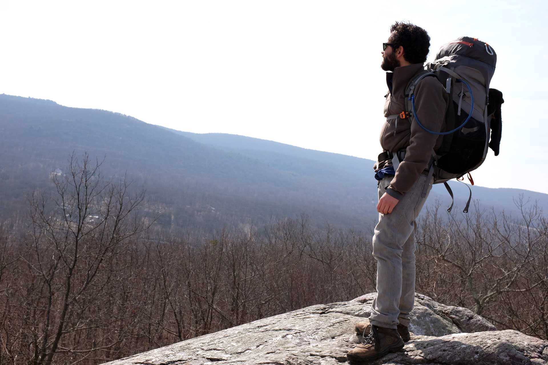 Photograph: the author stands at an overlook wearing a large backpack. Mountains are visible through haze in the far distance